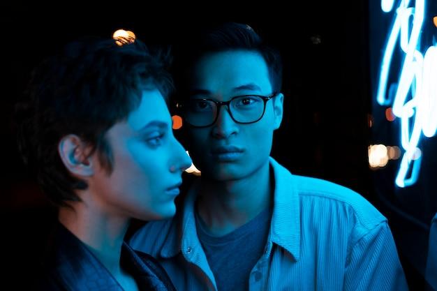 Para pozuje razem w nocy w niebieskim neonowym świetle