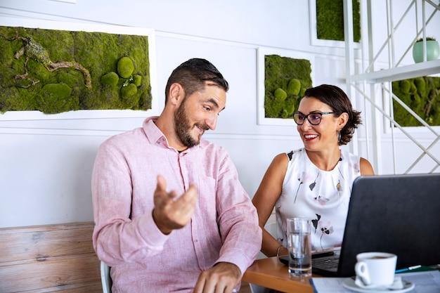 Para pracuje w domu za pomocą laptopa, pije kawę i rozmawia o pracy. spotkanie biznesowe w kuchni podczas wybuchu pandemii wirusa coronavirus