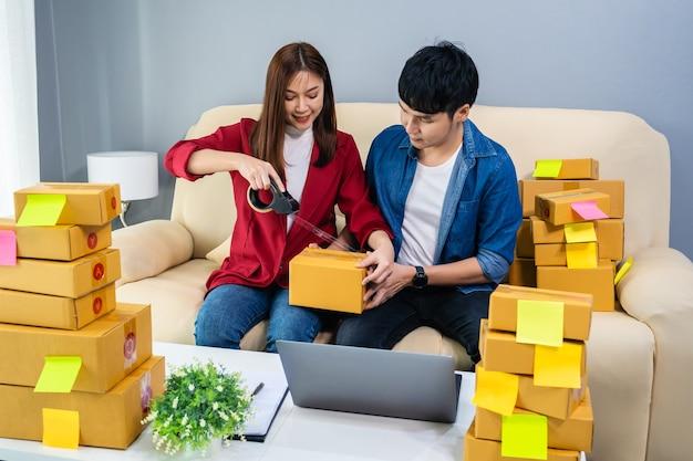 Para przedsiębiorcy online za pomocą taśmy do pakowania paczki w biurze domowym, przygotowuje produkt do dostawy do klienta