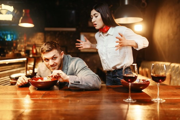 Para przy drewnianym barze, związek miłosny, kolacja z pastą i czerwonym winem. miłośnicy wypoczynku w pubie, mąż i żona w nocnym klubie