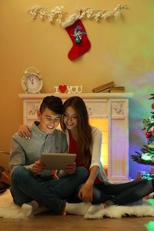 Para przy kominku w świątecznym domu z tabletem