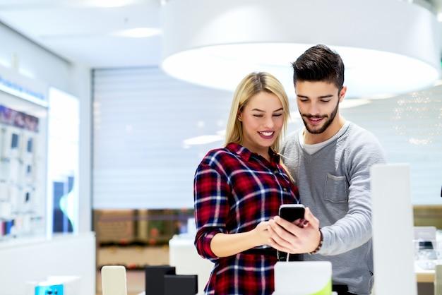 Para przy mobilnym sklepem kupuje nowego mądrze telefon. zakupy pojęcie przy zakupy centrum handlowym.