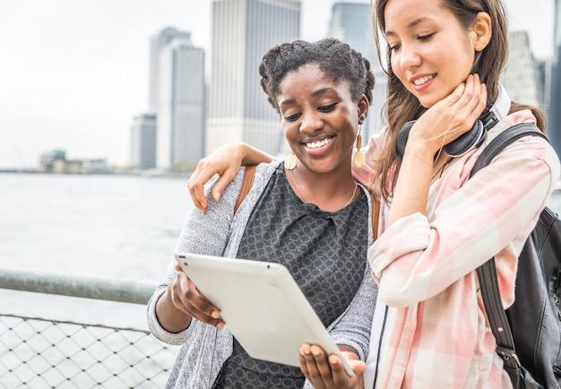 Para przyjaciele patrzeje pastylkę blisko do rzeki w nowym york mieście