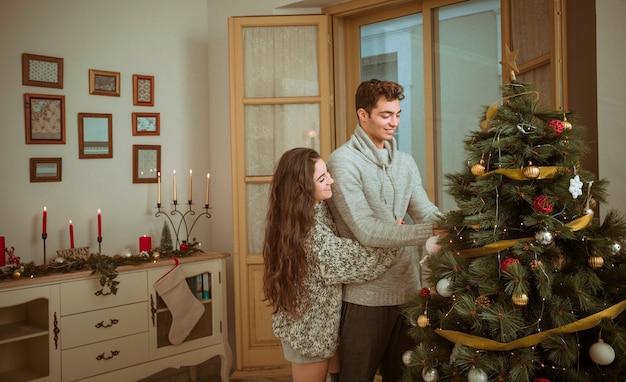 Para przytulanie podczas dekoracji domu na boże narodzenie