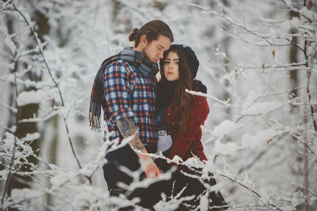 Para przytulanie siebie w zimowym lesie