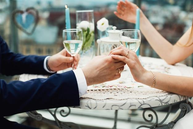 Para rąk na stole restauracji z dwiema lampkami szampana
