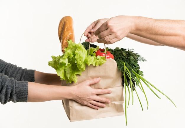 Para rąk, trzymając torbę spożywczą