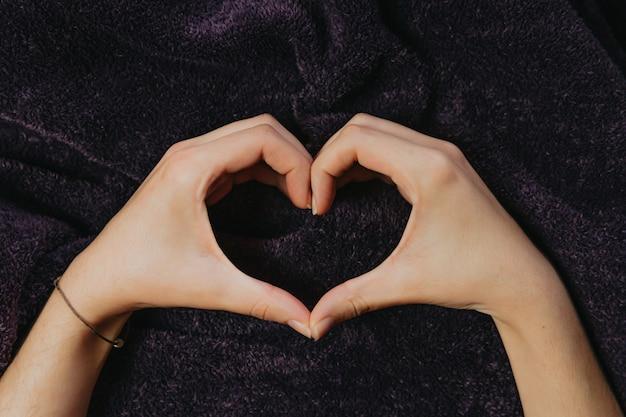 Para rąk tworzących serce na fioletowym kocu