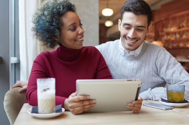 Para rasy mieszanej siedzi w kawiarni i udostępnia nowy film lub aplikację na tablecie pc