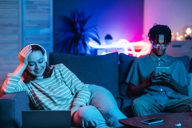 Para razem w domu na kanapie przy użyciu nowoczesnych urządzeń