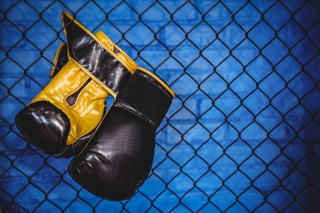 Para rękawic bokserskich wiszące na ogrodzeniu z siatki drucianej