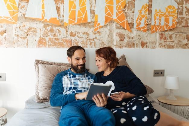 Para relaksował w domu w łóżku na pastylce i telefonie komórkowym