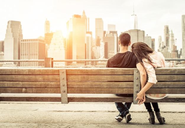 Para relaksujący na ławce w nowym jorku przed panoramą o zachodzie słońca. pojęcie o miłości, związku i podróżach