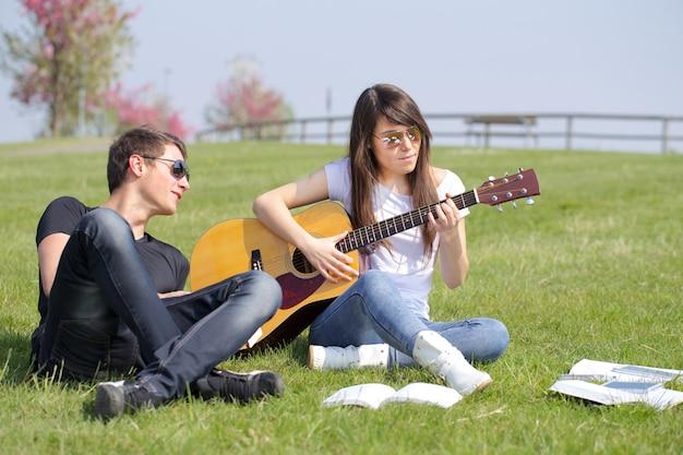Para relaksuje i bawić się gitarę plenerową