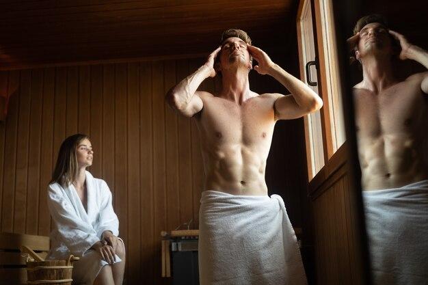 Para relaksuje się, odpoczywa i poci się w saunie