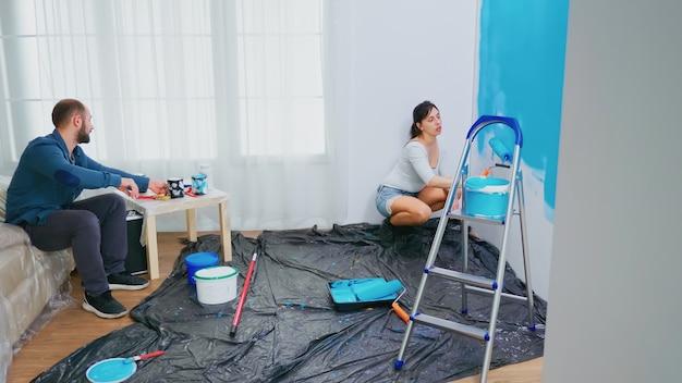 Para remontuje mieszkanie. zmiana koloru ściany. malowanie pędzlem wałkowym. para w dekoracji domu i renowacji w przytulnym mieszkaniu, naprawa i metamorfoza