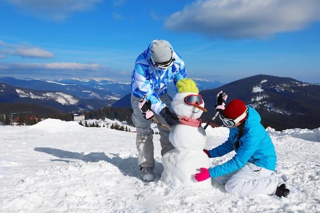 Para robi bałwana w ośrodku narciarskim. ferie zimowe
