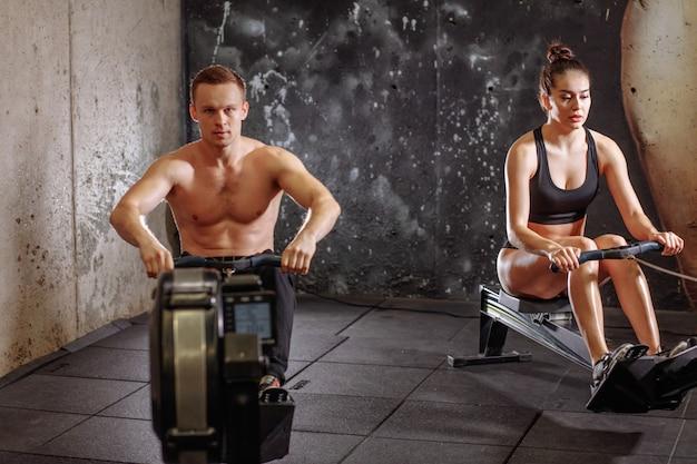 Para robi ćwiczeniom z wioślarską maszyną