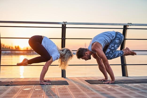 Para robi pozycję bakasany i wspólnie ćwiczy jogę na przyrodzie na świeżym powietrzu