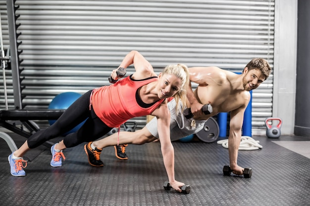 Para robi push up z hantlami na siłowni crossfit