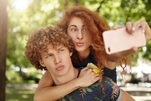 Para robi śmieszne miny podczas pozowania do selfie