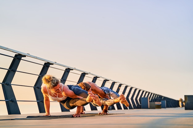 Para robi wspólne ćwiczenia jogi na przyrodzie na świeżym powietrzu poranne ćwiczenia o wschodzie słońca