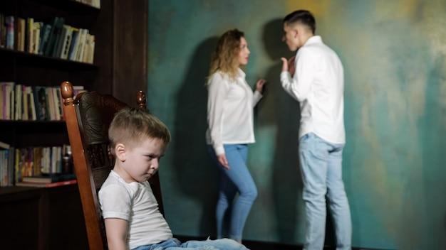 Para rodziców kłóci się przy swoim dziecku. smutny chłopczyk słucha krzyczących na siebie rodziców, siedząc na krześle, widok z boku.