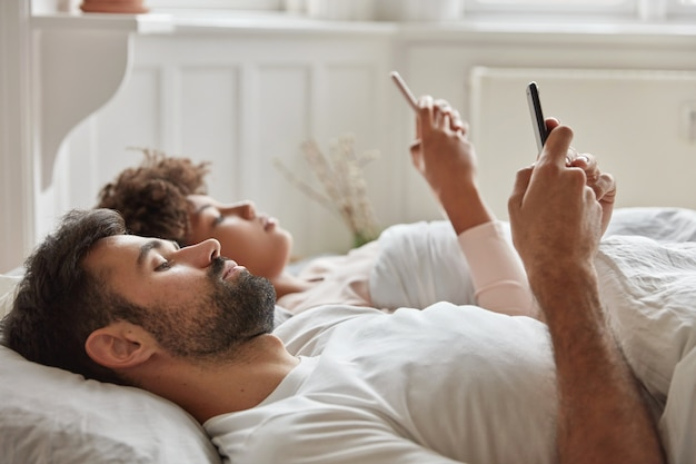Para rodzinna ignoruje ożywioną rozmowę przed snem, korzysta ze smartfona, ogląda wideo