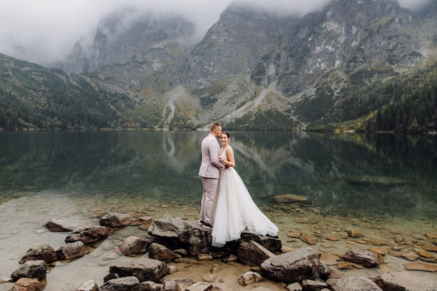 Para romantyczny ślub zakochany stojący nad jeziorem sea eye w polsce. tatry