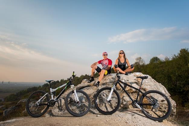 Para rowerzysta siedzi na skale, patrząc do kamery