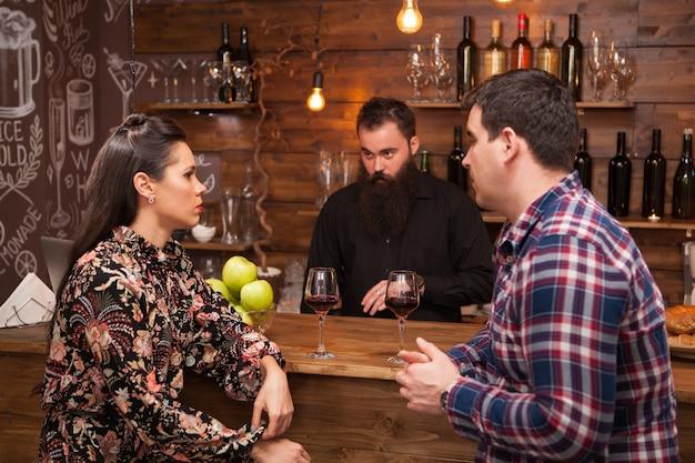 Para rozmawia z barmanem za ladą barową w kawiarni. hipsterski barman.