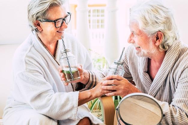 Para seniorów bawi się razem w zabiegu upiększającym pijąc koktajl i uśmiechając się - dwoje dojrzałych ludzi śmiejących się i relaksujących