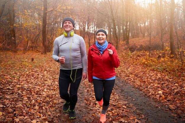 Para seniorów biega wśród leśnej ścieżki