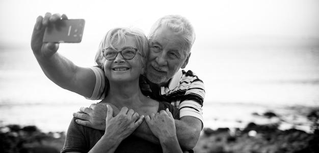 Para seniorów biorących salfie na plaży - szczęśliwa para emerytów cieszy się - kobieta w okularach