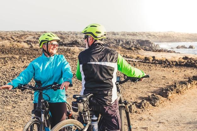 Para seniorów jedzie na rowerze o tej samej godzinie i zderzyła się i zaczęła rozmowę - dwie dojrzałe osoby ćwiczą razem, aby być sprawnym i zdrowym
