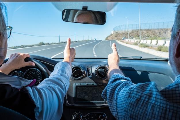 Para seniorów jeżdżących i bawiących się razem z wypożyczonym samochodem na ulicy - dwóch emerytów na wakacjach razem - mężczyzna i kobieta z palcem w górze - tak i koncepcja bezpiecznej jazdy