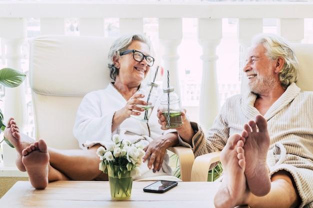 Para seniorów lub dojrzałych ludzi w spa w hotelu lub domu brzęcząca koktajlem lub napojem - bawi się z nogami na stole patrząc między sobą