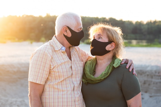 Para seniorów na plaży w masce medycznej w celu ochrony przed koronawirusem w letni dzień, kwarantanna koronawirusa