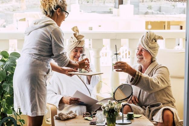 Para seniorów razem bawi się w hotelu w kurorcie z zabiegiem upiększającym i asystą kobiety - biorąc koktajl lub drinka na tarasie ich domu - patrząc na kobietę