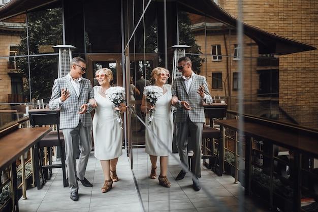 Para seniorów rodziny stojącej na tarasie w nowoczesnej kawiarni