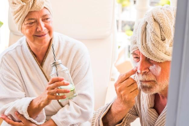 Para seniorów siedzi razem w hotelu ze spa i tratamentem urody - zbliżenie mężczyzny nakładającego krem na twarz z żoną patrzącą na niego