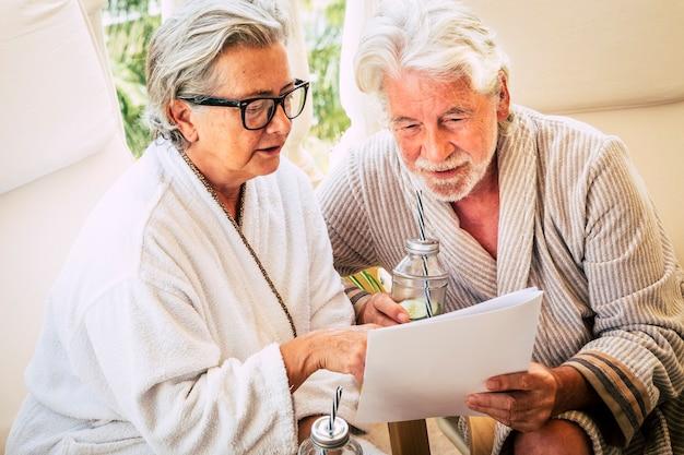 Para seniorów w domu lub kurorcie bawi się razem z zabiegami upiększającymi - wybierając z menu hotelu czekając na masaż