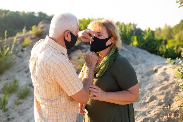 Para seniorów w maskach medycznych w celu ochrony przed koronawirusem w letni dzień