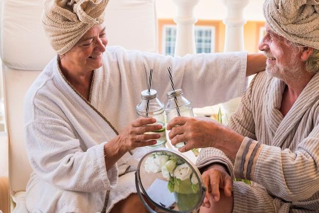 Para seniorów w salonie piękności razem przy koktajlu siedząc z kremem na twarzy dojrzałego mężczyzny - dwóch emerytów w farmie piękności