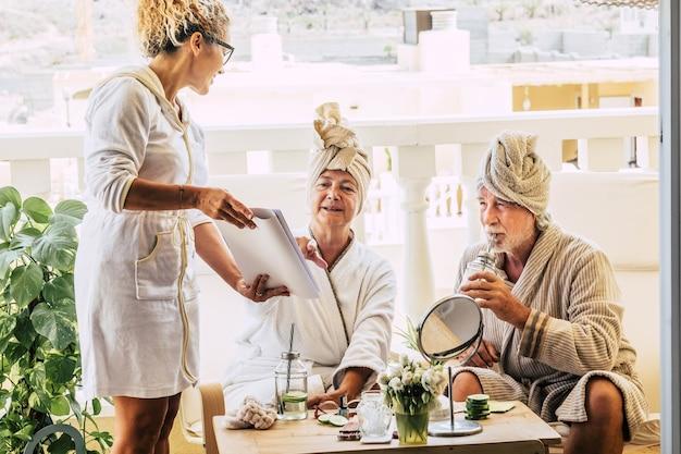 Para seniorów w trakcie zabiegu kosmetycznego wspólnie wybierająca coś z menu z asystentem pokazującym im gazetę