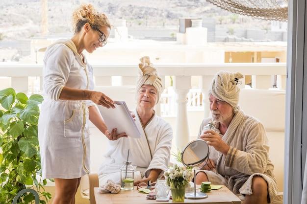 Para seniorów wspólnie bawi się w hotelu w kurorcie z zabiegiem kosmetycznym i asystą kobiety - przy koktajlu lub drinku na tarasie ich domu