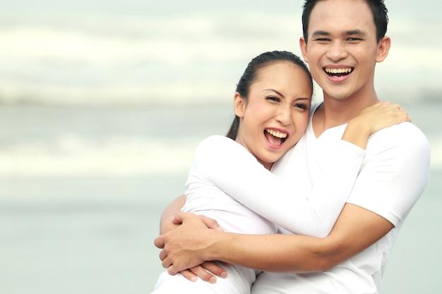 Para się śmiać, ciesząc się wakacje na plaży