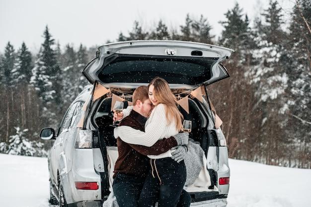 Para siedząca z kubkami z tyłu samochodu i piknik w śnieżnym lesie