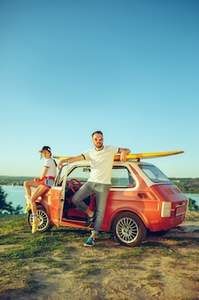 Para siedzi i odpoczywa na plaży w letni dzień, w pobliżu rzeki. miłość, szczęśliwa rodzina, wakacje, podróże, koncepcja lata.