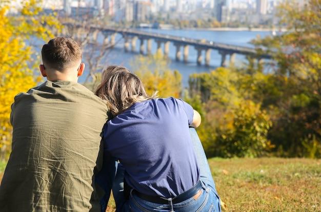 Para siedzi i patrzy na widok na kijowski most. jesienna stolica ukrainy. koncepcja miłości. krajobraz miasta z rzeką dniepr.
